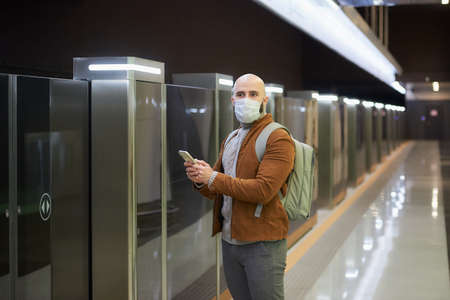 A man in a medical face mask is holding a phone and staring to the side while waiting for a train at the subway platform. A bald guy in a surgical mask is keeping social distance.