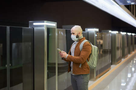 A man in a medical face mask is reading news on a smartphone and staring to the side while waiting for a train at the subway platform. A bald guy in a surgical mask is keeping social distance. Standard-Bild