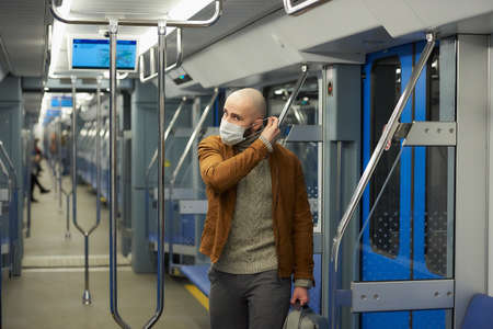 A man with a beard is putting on a medical face mask to avoid the spread of in a subway car. A bald guy in a surgical mask against  is keeping social distance on a train. Standard-Bild