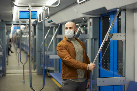 A man with a beard in a medical face mask to avoid the spread of is staring to the side and holding the handrail in a subway car. A bald guy in a mask is keeping social distance on a train Standard-Bild