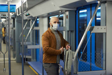 A man with a beard in a medical face mask to avoid the spread of is putting on a backpack while riding a subway car. A bald guy in a surgical mask is keeping social distance on a train.