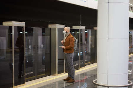 A full-length photo of a man in a face mask is holding a smartphone while waiting for a train at the subway platform. A bald guy in a surgical mask is keeping social distance. Standard-Bild