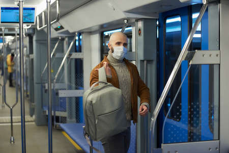 A man with a beard in a face mask to avoid the spread of is putting on a backpack while riding a subway car. A bald guy in a surgical mask is keeping social distance on a train.
