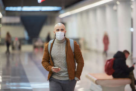 A man in a medical face mask is holding a smartphone and walking while waiting for a train in the center of the subway station. A bald guy in a surgical mask is keeping social distance. Standard-Bild