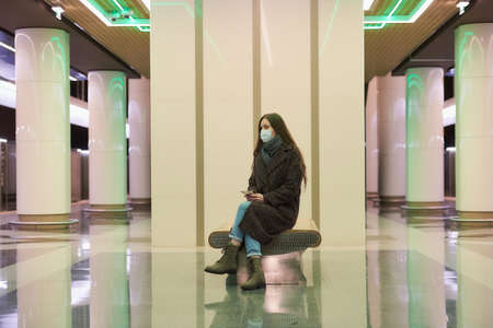 A lonely woman in a medical face mask to avoid the spread of is sitting with a smartphone on the subway platform. A girl in a surgical mask is keeping social distance in the metro. Standard-Bild