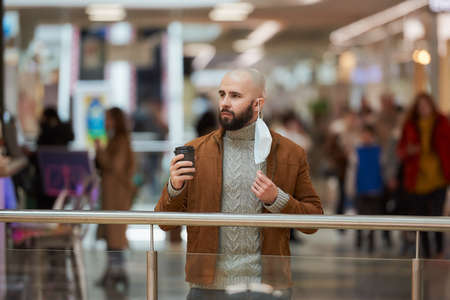 A man is holding a took-off medical face mask while sipping coffee in the shopping center. A bald guy is keeping social distance.