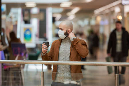 A man with a beard is putting on a medical face mask while holding a brown cup of coffee in the shopping center. A bald guy is keeping social distance.