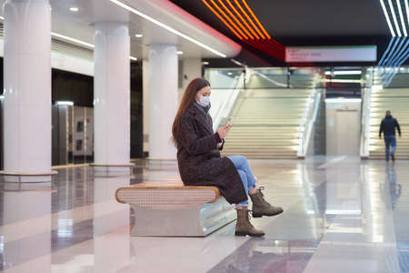 A woman in a medical face mask is sitting in the center of the subway platform and using a smartphone. A girl with long hair in a surgical mask is keeping social distance in the metro.