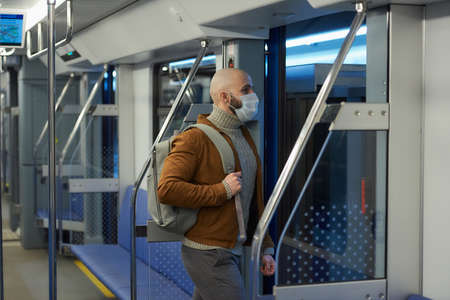 A man with a beard in a face mask to avoid the spread of is leaving a subway car. A bald guy in a surgical mask is keeping social distance on a train. Standard-Bild