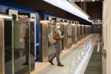 A man in a medical face mask to avoid the spread of  is holding a cellphone while leaving a modern subway car. A bald guy in a surgical mask is keeping social distance.