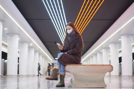 Woman in a medical face mask is sitting in the center of the big subway station with a smartphone and reading the news. A girl with long hair in a surgical mask is keeping social distance in the metro