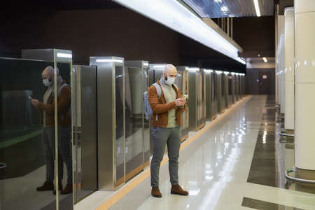A full-length photo of a man in a face mask who is scrolling the smartphone while waiting for a train at the subway platform. A bald guy in a surgical mask is keeping social distance.