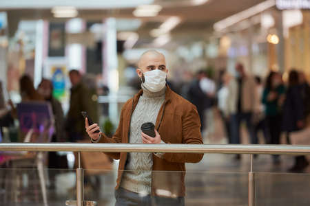 A man with a beard in a face mask is looking to the right and holding a smartphone and a cup of coffee in the shopping center. A bald guy in a surgical mask is keeping social distance.