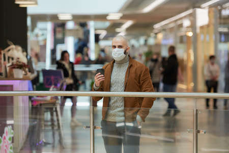 A man in a face mask to avoid the spread of is holding a cup of coffee in the shopping center. A bald guy in a surgical mask is keeping social distance.