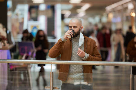 A man is holding a took-off medical face mask while drinking coffee in the shopping center. A bald guy is keeping social distance.