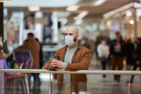 A man in a face mask to avoid the spread of  shopping center. A bald guy in a surgical mask is keeping social distance.
