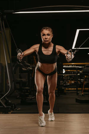A sporty woman with long blonde hair is doing a chest workout on the cable machine in a gym. A girl is training her pectoral muscles.