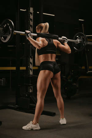 A photo from behind of a sporty woman with blonde hair who is started squatting with a barbell near the squat rack in a gym. A girl is doing a leg workout. Standard-Bild