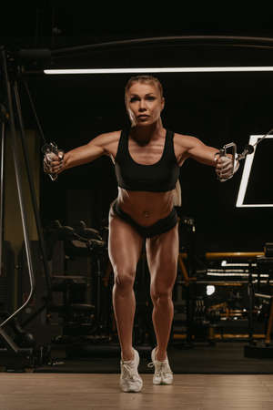 A sporty woman with blonde hair is doing a chest workout on the cable machine in a gym. A girl is training her pectoral muscles. Standard-Bild