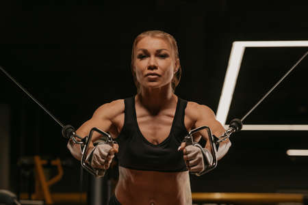 A close-up photo of a fit woman with blonde hair who is doing a chest workout on the cable machine in a gym. A girl is training her pectoral muscles.