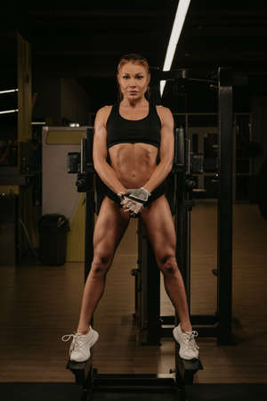 A sporty woman with blonde hair is posing in a gym. A girl is relaxing after a workout.