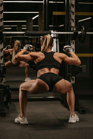 A photo from behind of a sporty woman with blonde hair who is warming up before squatting with a barbell near the squat rack in a gym. A girl is doing a leg workout. Standard-Bild