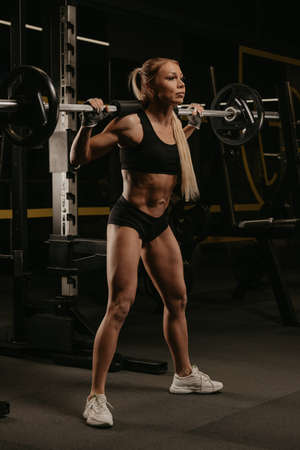 A sporty woman with blonde hair is started squatting with a barbell near the squat rack in a gym. A girl is doing a leg workout.