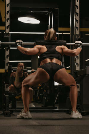 A photo from behind of a sporty woman with blonde hair who is squatting with a barbell near the squat rack in a gym. A girl is doing a leg workout.