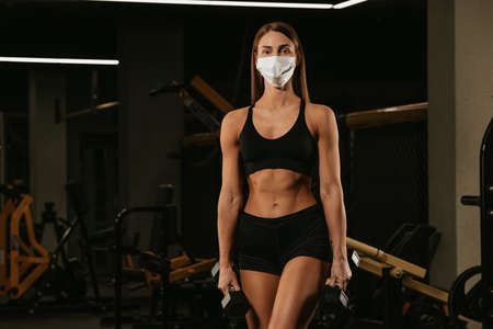 A fit woman in a face mask to avoid the spread of coronavirus is posing with dumbbells. A sporty girl in a surgical mask is posing after the arms workout in a gym.