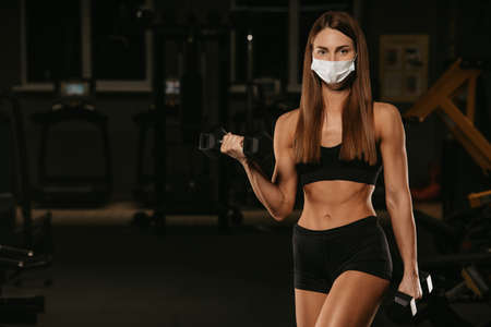 A fit woman in a face mask to avoid the spread of coronavirus is doing bicep curls with dumbbells. A sporty girl in a surgical mask is posing during the arms workout in the gym. Standard-Bild