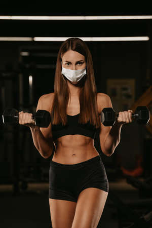 A fit woman in a face mask to avoid the spread of coronavirus is doing bicep curls with dumbbells. A sporty girl in a surgical mask is posing during the arms workout in a gym. Standard-Bild