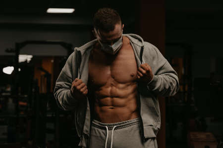 A bodybuilder in a face mask to avoid the spread of coronavirus is opening his zipped hoodie to demonstrate his athletic physique. A sporty guy in a surgical mask is posing after a workout in a gym.