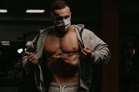 A bodybuilder in a face mask to avoid the spread of coronavirus is opening his zipped hoodie to demonstrate his vacuum workout. A sporty guy in a surgical mask is posing after training in a gym.