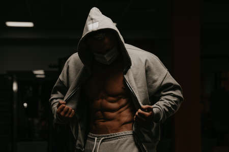 A bodybuilder in a hood and a face mask to avoid the spread of coronavirus is opening his zipped hoodie to demonstrate his abdominal muscles. A sporty guy in a surgical mask is posing after a workout