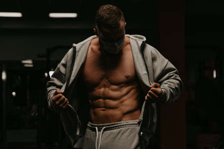 A bodybuilder in a face mask to avoid the spread of coronavirus is opening his zipped hoodie to demonstrate his abdominal muscles. A sporty guy in a surgical mask is posing after a workout in a gym.