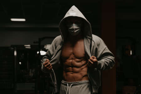 A bodybuilder in the hood and a face mask to avoid the spread of coronavirus is opening his zipped hoodie to demonstrate his abs. A sporty guy in a surgical mask is posing after a workout in a gym. Foto de archivo