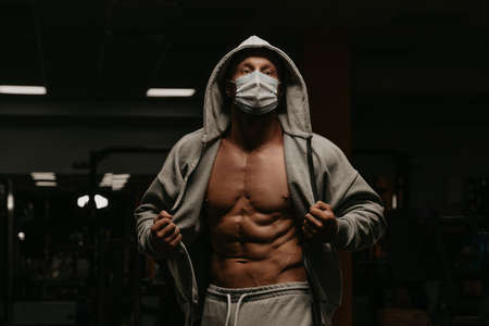 A bodybuilder in a hood and a face mask to avoid the spread of coronavirus is opening a hoodie to demonstrate his athletic physique. A sporty guy in a surgical mask is posing after a workout in a gym.
