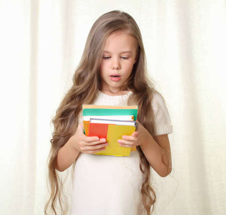 amaze: Little blond girl holding different books and looking on it with amaze Stock Photo