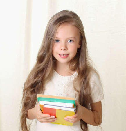 mixed age: Little blond girl holding diffenet books and smiling Stock Photo