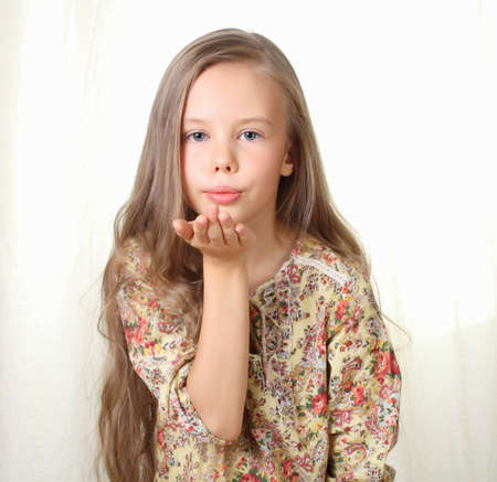 blow kiss: Little blond girl sends air kiss and blowing Stock Photo