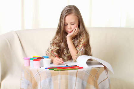 females only: Little blond girl drawing at home on sofa
