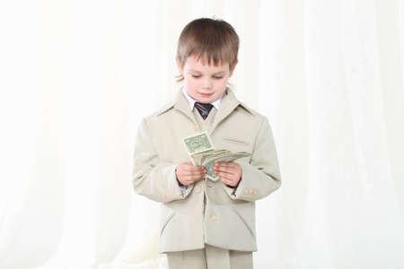 Piccolo ragazzo intelligente in tuta mostrando dollari