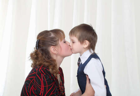 Little son in smart suit kissing his mother photo