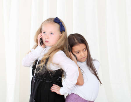 Two little girls calling by phone to each other photo