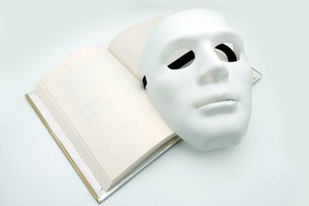 pantomima: Máscara blanca teatral en el libro abierto con páginas en blanco