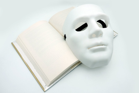 White theatrical mask on open book with blank pages
