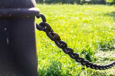 pillar with black iron chain on grass background. industrial, nature.