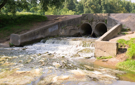 environmental issues: stone pond drainage with small waterfall. background, nature. Stock Photo