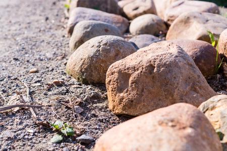 fenceline: border of stones near the walkway. nature, peace.