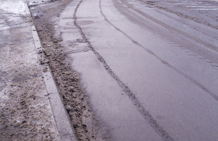 polluted snow on the road with car traces. background, seasonal. Reklamní fotografie